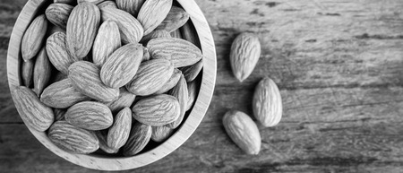 Almonds in brown bowl on textured wooden background, top view. banner panoramic crop for copy space. Stock Photo