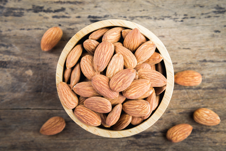 Almonds in brown bowl on textured wooden background, top view.