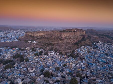 Aerial view of Mehrangarh Fort at sunset sits above the 'Blue City' Jodhpur, Rajasthan State India.