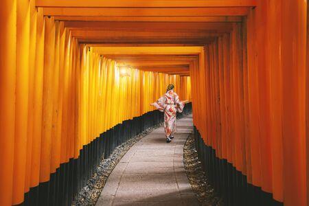 Yong Women in traditional japanese kimonos walking at Fushimi Inari Shrine in Kyoto, Japan