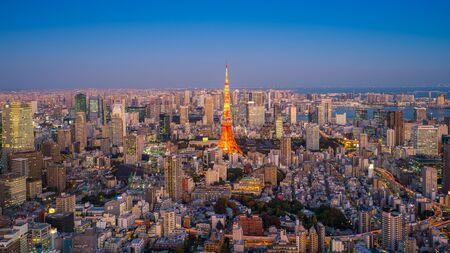 Tokyo Tower z budynków miasta w Tokio, Japonia w Zmierzchu. Zdjęcie Seryjne