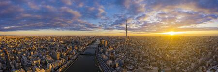 Aerial panorama view by drone of Tokyo Cityscape with Tokyo Sky Tree visible in Tokyo city, Japan on sunrise. Panoramic Dawn view of Tokyo city. Famous Tokyo Skytree and Senso-Ji Temple with Sumida river. Colorful morning scene of Japan, Asia.