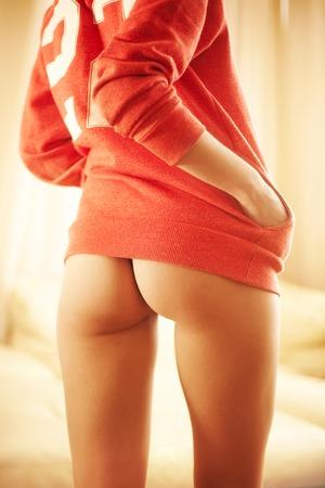 female buttocks: female buttocks under red baseball pullover