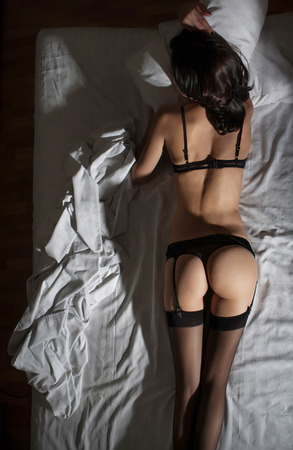 nude female buttocks: attractive woman in stockings lyinng in the bed Stock Photo