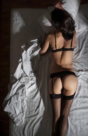 nackt: attraktive Frau in Str�mpfen lyinng im Bett