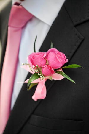 buttonhole: wedding rose boutonniere in grooms tuxedo with rose tie Stock Photo