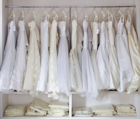 cream colored: white and cream colored bridal dresses on hangers Stock Photo