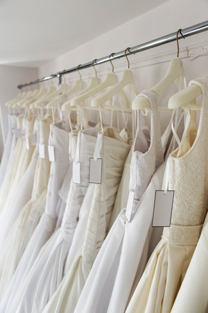 wedding dress: white and cream colored bridal dresses on hangers Stock Photo