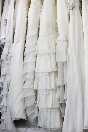 elegant dress: white and cream colored bridal dresses on hangers Stock Photo
