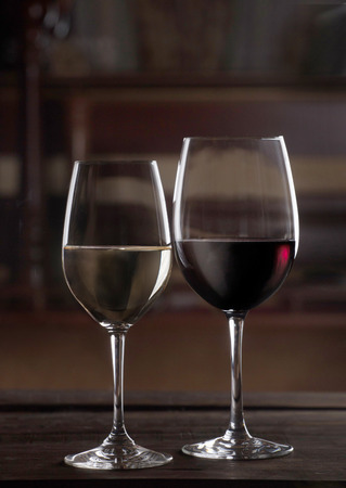 Glasses of red and white wine on wooden background in restarant space
