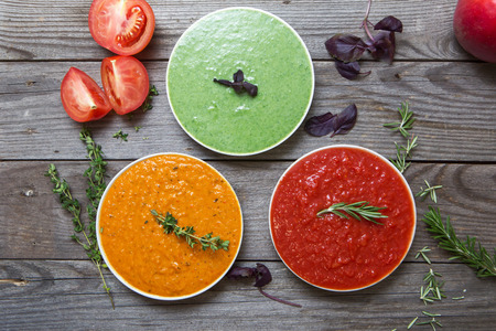 Variety of colorful vegetables cream soups and ingredients for soup. Top view. Concept of healthy eating or vegetarian food