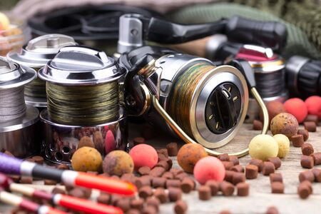 fishing tackle on a wooden table. toned image