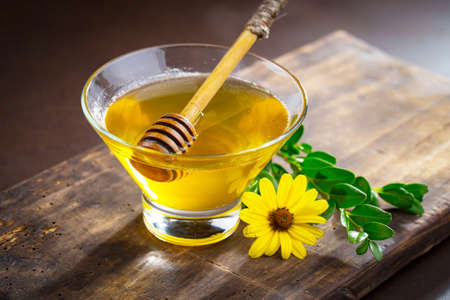 Sweet honey with flowers on an old background.