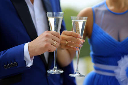 poured: The groom in a blue suit and the bride in a blue dress standing with glasses in which is poured the champagne
