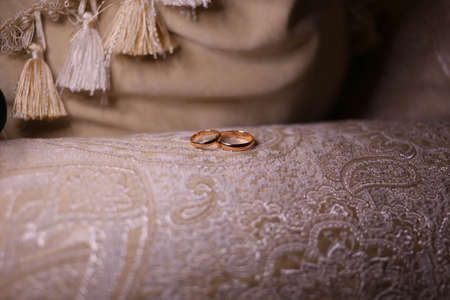 wedding bands: gold wedding rings, wedding bands on a yellow background, rings on the couch
