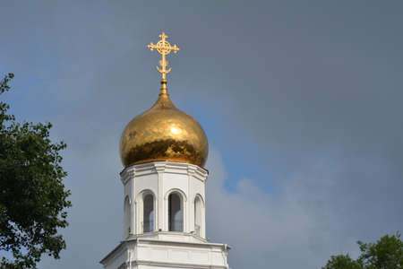golden section: Top of Russian church from red bricks with golden cupola over clear blue sky closeup Stock Photo