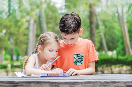 hapy: Hapy kids  learn in a park. Brother and sister together do the job. Boy and girl sitting at the table and doing exercise. Stock Photo