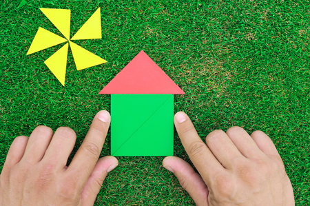 House and sun made of tangram figures on natural grass. Mans hands
