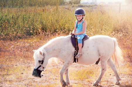 gait: Little girl on the horse. White poni.
