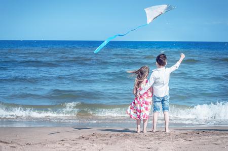 Niño y niña en la playa con una cometa. La libertad, infancia despreocupada y esperanza. Hermano y hermana juntos.