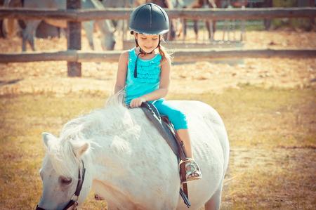 Reizendes Mädchen auf einem Pferd. Kind und Aimal. Litlle-Mädchen, das ein Pferd in der Landschaft reitet.