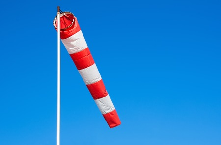 airstrip: Airport windsock on clear blue sky background.  Air sock, drogue, wind sleeve, wind cone Stock Photo