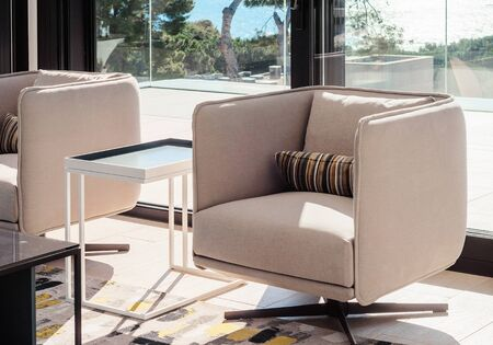 Modern living room interior with swivel chairs and coffee table, opposite window overlooking the sea. Details of the decor in a luxury home. Decor background. Standard-Bild