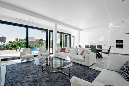 Luxurious and modern living room, dining with large windows with access to the pool. . Luxurious furniture, sofa, table and chairs.