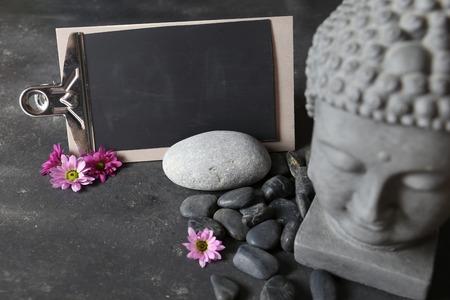 cabeza de buda: buddha head with stones , flowers and tabular Foto de archivo