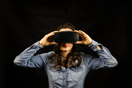 mediated: Single young woman holding large 3D virtual reality viewing device over face on black background