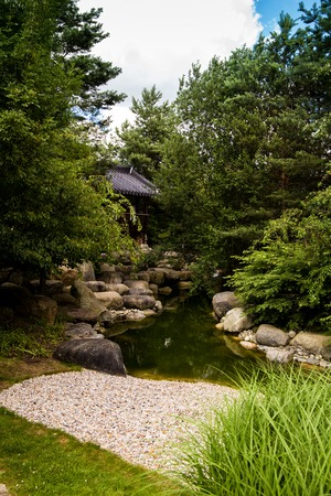 Natural small brook in park with chinese house