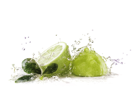 Green limes with splashing water Stock Photo