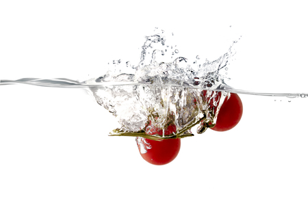Closeup of fresh and health tomatoes falling into clear water with big splash
