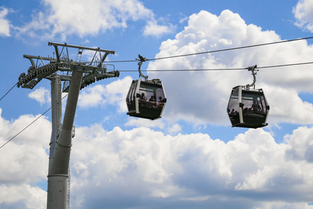 A cablaway with two cable car on a partly cloudy blue sky