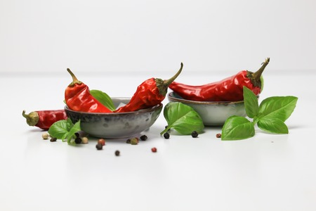 chilli pepper and basil leaves still life isolated on white backgroun Stock Photo