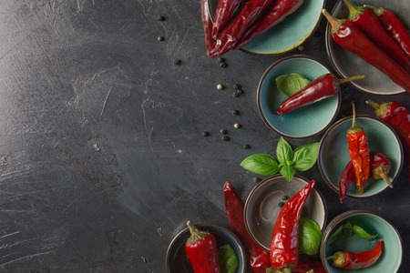 chili peppers with basil and peppercorns in bowls on a rustic surface,