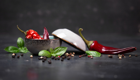 chili peppers with basil and peppercorns in bowls on a rustic surface, Stock Photo - 116308172