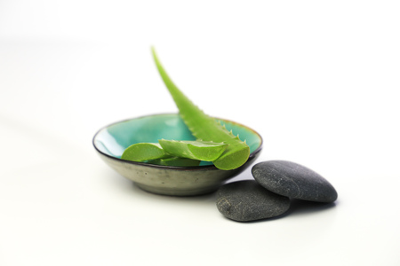 aloe vera leaves in a small bowl, with spa stones on a white background Stockfoto - 127695280