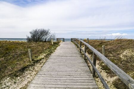 Wooden path at Baltic sea over sand dunes with ocean view Stockfoto - 127695317