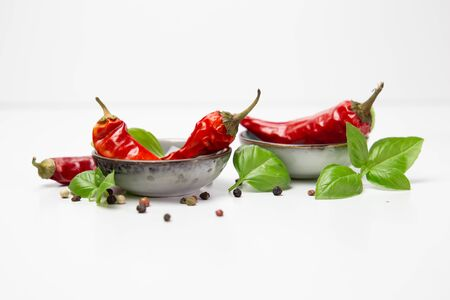 chilli pepper in bowls and basil leaves still life isolated on white background