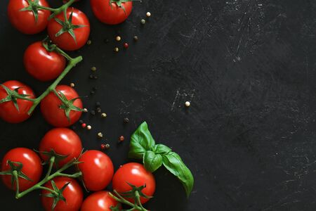 Fresh tomatoes on a black background with spices. Top view. Standard-Bild