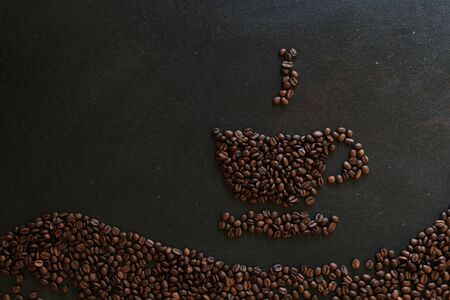 coffee beans in the shape of a cup on dark background 写真素材