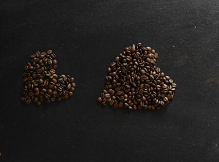 coffee beans in the shape of a heart on dark background