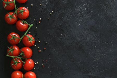 Fresh tomatoes on a black background with spices. Top view. 写真素材