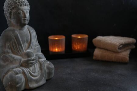 Buddha with candle and towel spa concept