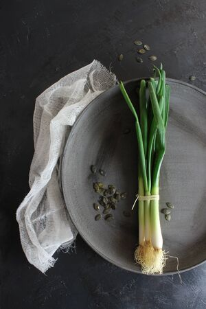Spring onions on dark table