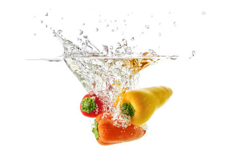 Red and orange peppers fall into the water with splashes and bubbles.