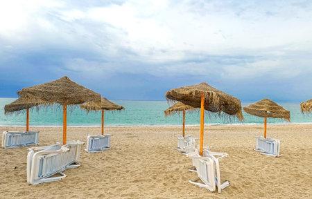white plastic sun loungers, sun umbrellas on the beach.