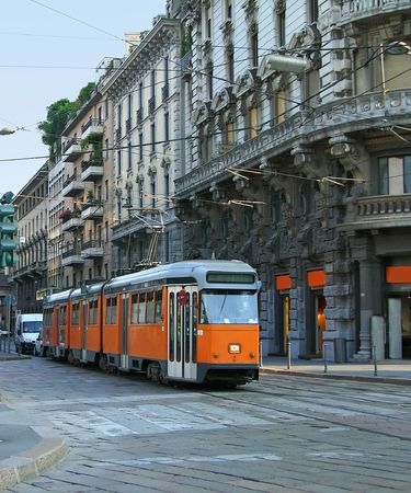 Milan street with old orange tram, Italy