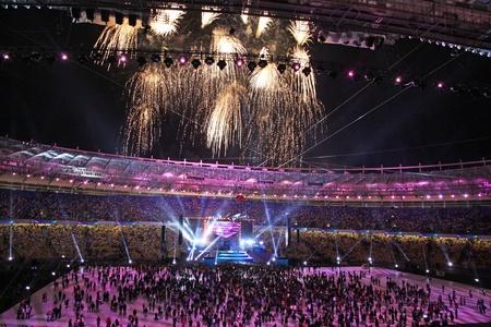 spectators: Kiev, Ucrania - 8 de octubre de 2011: Los espectadores ver los fuegos artificiales al final de la ceremonia de apertura de los principales Euro-2012 arena - Estadio Ol�mpico (NSC Olimpiysky) Editorial
